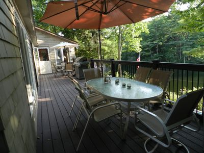 New deck with two tables, gas grill, & seating for 12. Sunroom entrance at end.