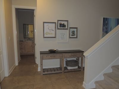 Front Entryway with bathroom in the background and stairs on the right.