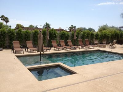 Large salt water pool with baja step and plenty of chaise lounge chairs
