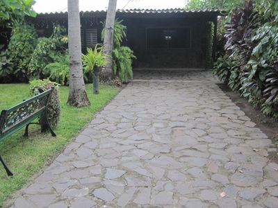 driveway to the house. Front has beautiful patio looking out to lush gardens.