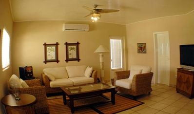 Condo living room: Air conditioning, flat screen TV and plush couch / chairs