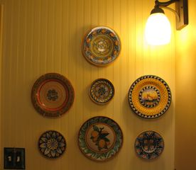 Healdsburg cottage photo - This collection of handpainted plates creates a colorful backdrop for the stove.