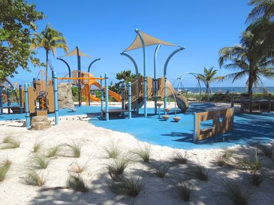 New children's play area is next to adult exercise equipment at the beach.