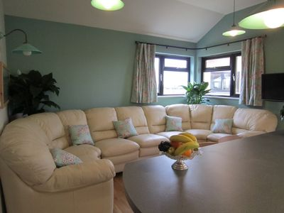 Cheddar chalet rental - curl up on the comfy leather sofas/meadow view
