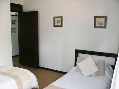 twin bedroom with door leading to main bathroom