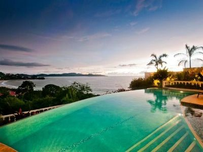 Infinity edge pool with jacuzzi and beach/ocean views