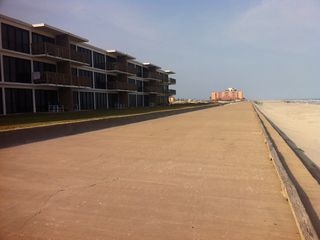 North Padre Island condo photo - One mile seawall out front with Holiday Inn in distance with live bands .