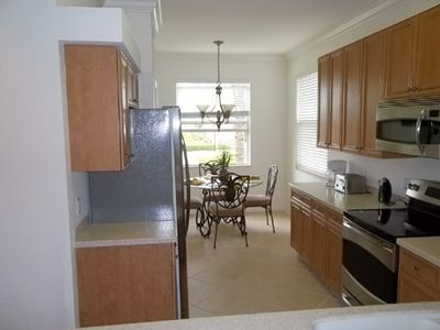 Eat in kitchen with stainless appliances, solid surface counters, & side window!