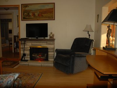 Living room with electric fireplace. Shows entrance to kitchen right,bdrm lef...