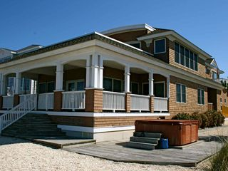 View of back of house including hot tub and wrap around porch, bay is behind me - Holgate house vacation rental photo