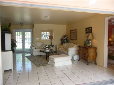 Bright spacious livingroom with TV and full sliding doors to pool