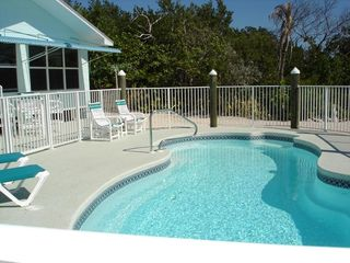 Little Torch Key house photo - Fenced heated pool with fiber optic lighting on water side of house.