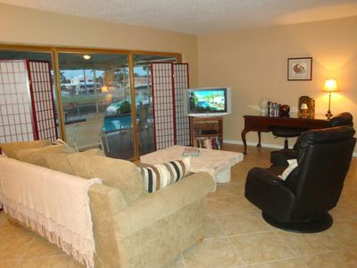 Living room opens to pool deck and has queen sleeper sofa.