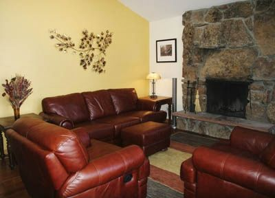 Spacious living room with high-quality new leather furniture and stone fireplace