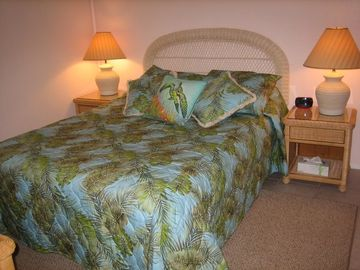 The comfortable bedroom with queen-sized bed and tropical furnishings