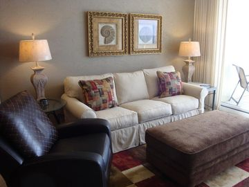 Fort Morgan condo rental - Living room with new area rug, couch slipcover and ottoman.