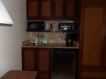 Kitchenette with custom shelf for microwave and toaster oven.