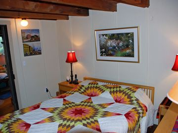 MBR on first floor; queen bed; closet; dresser; window with pine forest view.