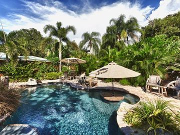 Private tropical lagoon with waterfall, beach entry, baja ledge and swim up bar