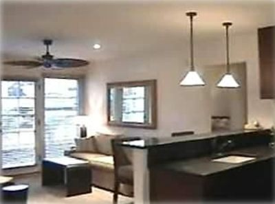 Kitchen and living room.  Granite counter tops, berber carpet, stone floors.
