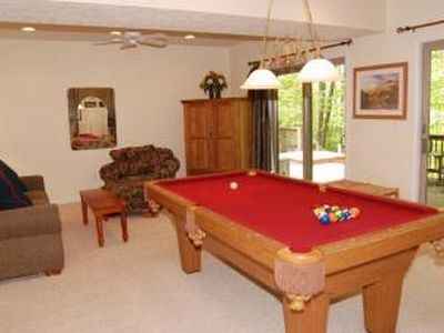 Pool table in the basement with a wet bar