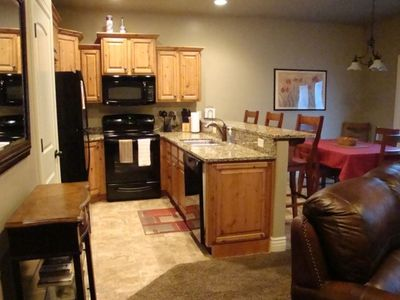Kitchen/Dining area with granite countertop & three bar stools.