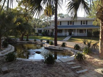 Naples house rental - front of house with lagoon pond, featuring fountain and waterfall at other end