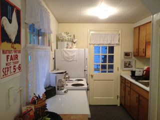 Galley Kitchen with butcher's block, electric stove and full-sized fridge. - Oak Bluffs house vacation rental photo