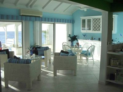"Pelican Key villa rental - Picture of dining and ""sitting"" areas with the deck and turqoise sea beyond."