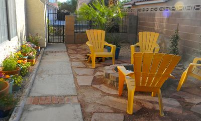 Side yard seating around real wood fire-pit, and flower garden