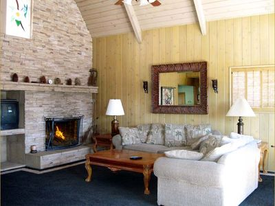 Lake Arrowhead estate rental - Spacious living room with large fireplace and views of the lake