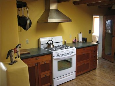 The white stove sets off the green slate countertops.