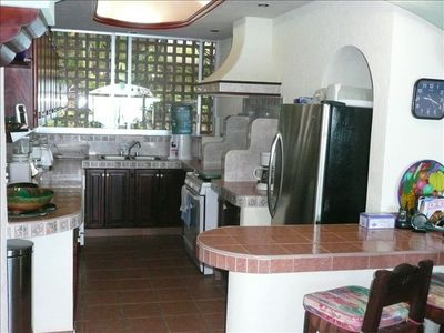View of large kitchen, window facing mountain