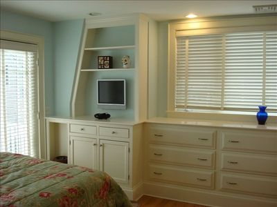 bedroom with built-in cabinets and TV system