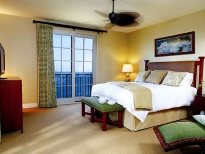 Spacious master bedroom with a lounging area and relaxing ocean views.