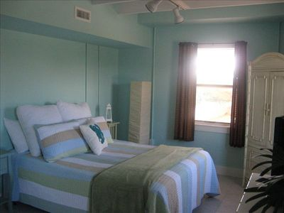 Spacious master bedroom with spa like decor has private bath and flat screen tv