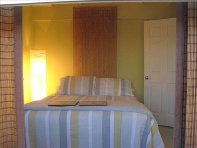 Guest Bedroom with restful beachy decor, comfy queen size bed and flat screen tv