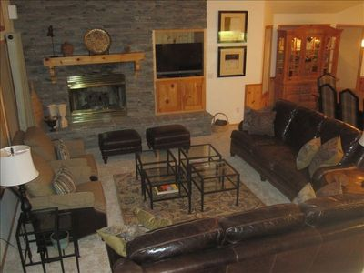 Great room living area with gas fireplace, flat screen TV, long leather sofas.