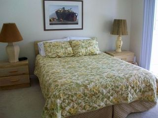 Queen size bed in the Master bedroom w/ screened-in lanai. TV in bedroom