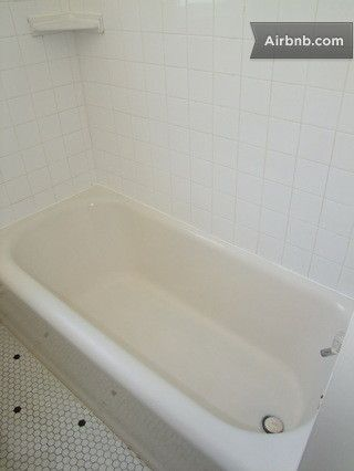 Deep iron tub, tile surround, hexagonal tile floor