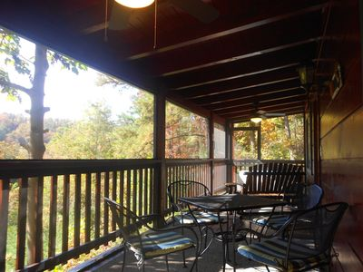 Screened-in porch with hot tub, swing/glider, dining area, ceiling fans, etc.