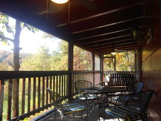 Pigeon Forge cabin photo - Screened-in porch with hot tub, swing/glider, dining area, ceiling fans, etc.