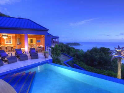 Infinity edge pool and covered outdoor dining areas overlooking the Caribbean