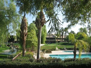 Palm Desert condo rental - View of the waterfall, lake, pool, and clubhouse from our front door.