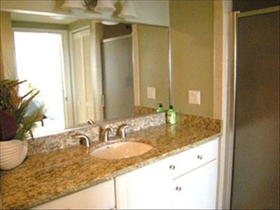 Master Bath with granite countertops, tiled shower, and access to washer/dryer