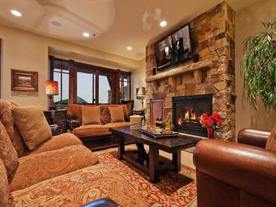 Living room with luxury furnishings, gas fireplace, flatscreen TV and balcony.