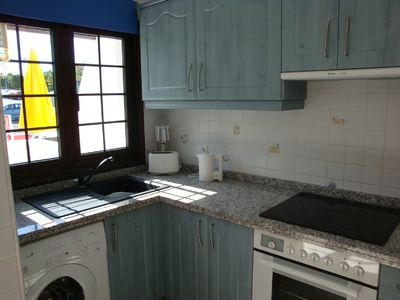 Kitchen with washing machine, microwave & fridge