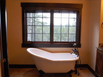 Master bathroom with antique style tub, walk-in marble shower, heated floor tile