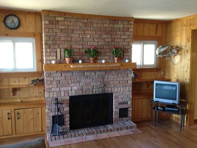 Living room brick fireplace. Cozy up and watch Direct TV on rainy afternoons