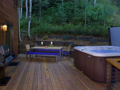 Private back deck has a gas grill, table & seating for 10 & a large hot tub